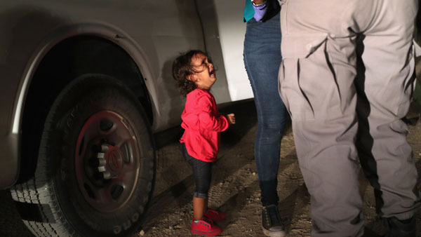 (Pulitzer Prize-winning Getty photographer John Moore took this instantly iconic shot of a 2-year-old Honduran asylum seeker crying as her mother is searched and detained last week.)